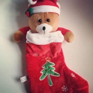 En rød julesok med en bamse kiggende op fra sokken