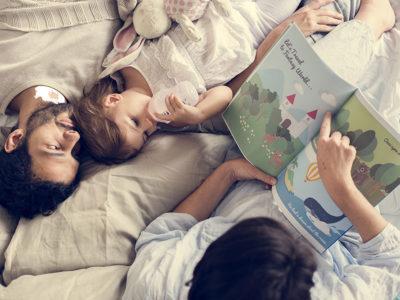 Mor far og barn læser historie